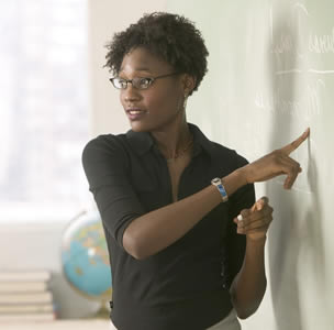 A teacher talking to the class while standing at the blackboard
