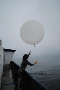 Recent graduate launching a balloon from a NOAH research vessel.