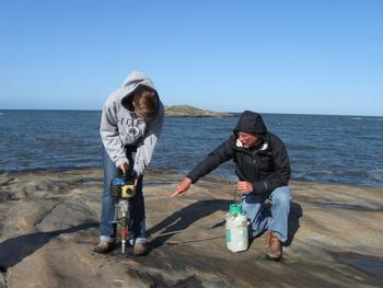 Student researcher collecting samples with a rock drill from a glacially polished outcrop, Halland Province, Sweden
