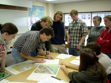 Cam Davidson and a few of his students discussing a map