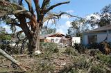 Broken tree limbs and damaged house caused by a tornado