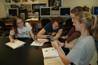 students measuring temperature of compressed gas as it is released from can