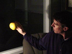 A grapefruit illuminated by a lightbulb shows phases too