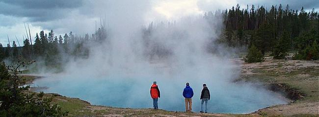 Scientists standing along a thermal pool in Yellowstone National Park