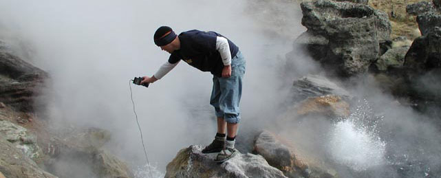 Researcher checking temperature of hydrothermal feature.