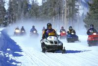 Snowmobiles led by a guide in Yellowstone National Park.